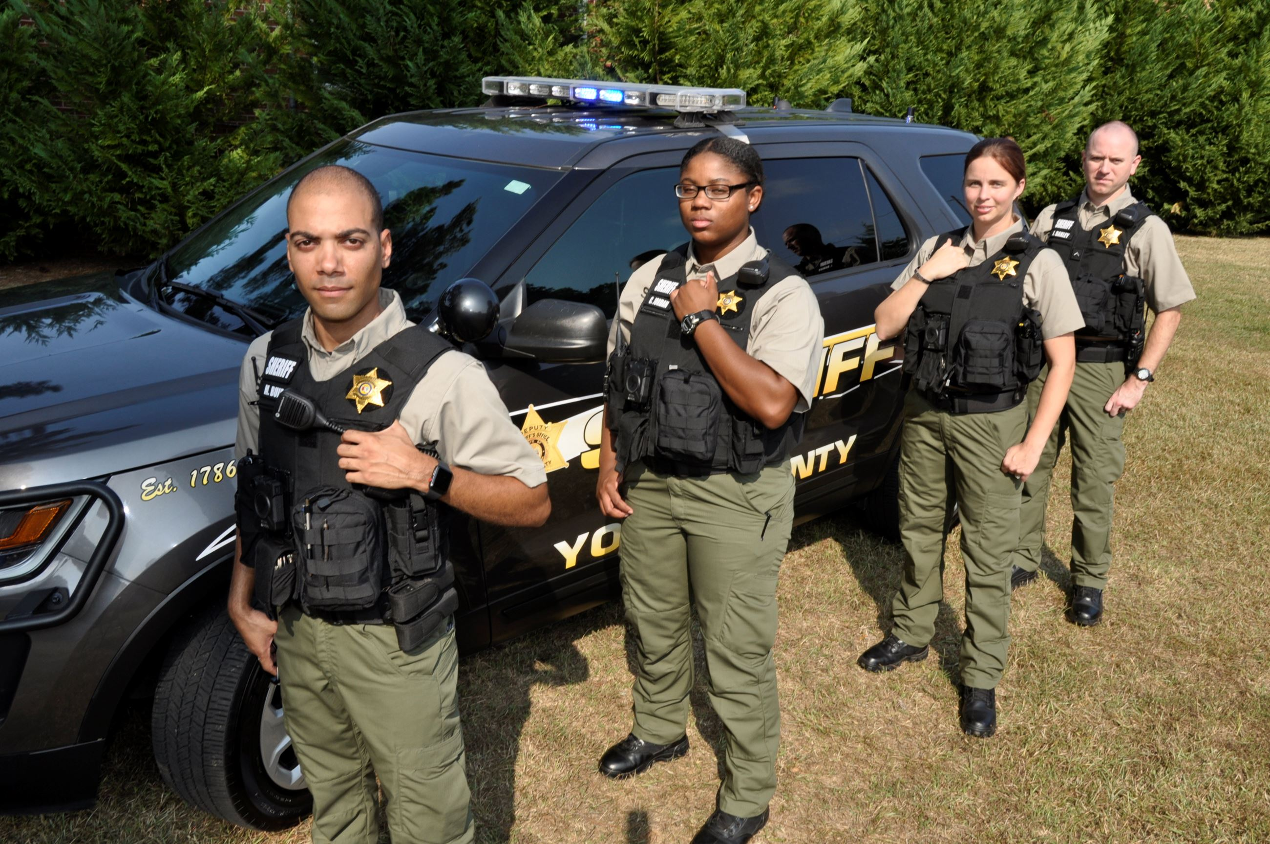 Four Deputies in the new Sheriff's Office uniforms standing in front of a SUV patrol car