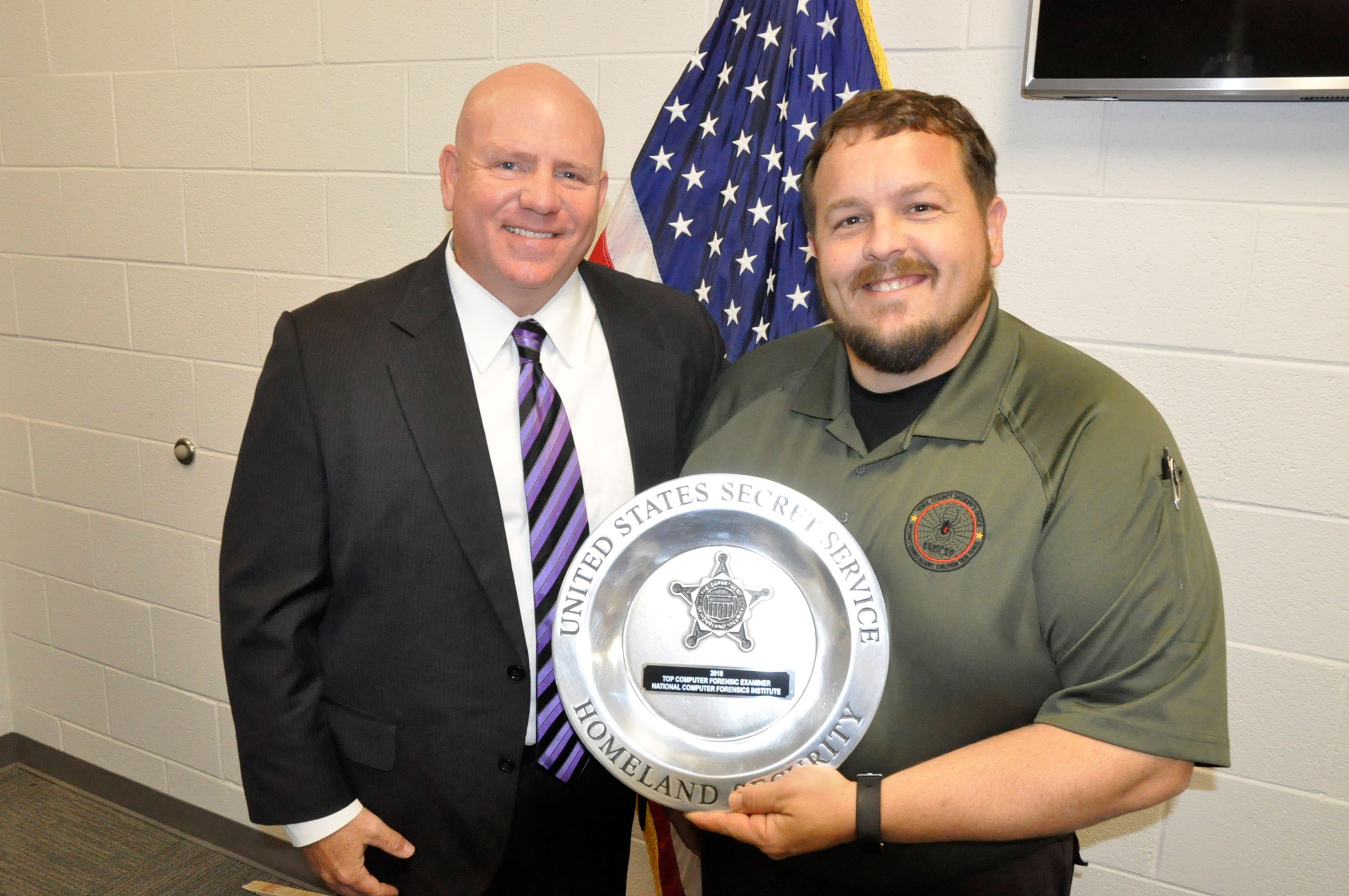 Photo of Special Agent Frank Kelley and Detective Alex Clark holding Silver Plate Award